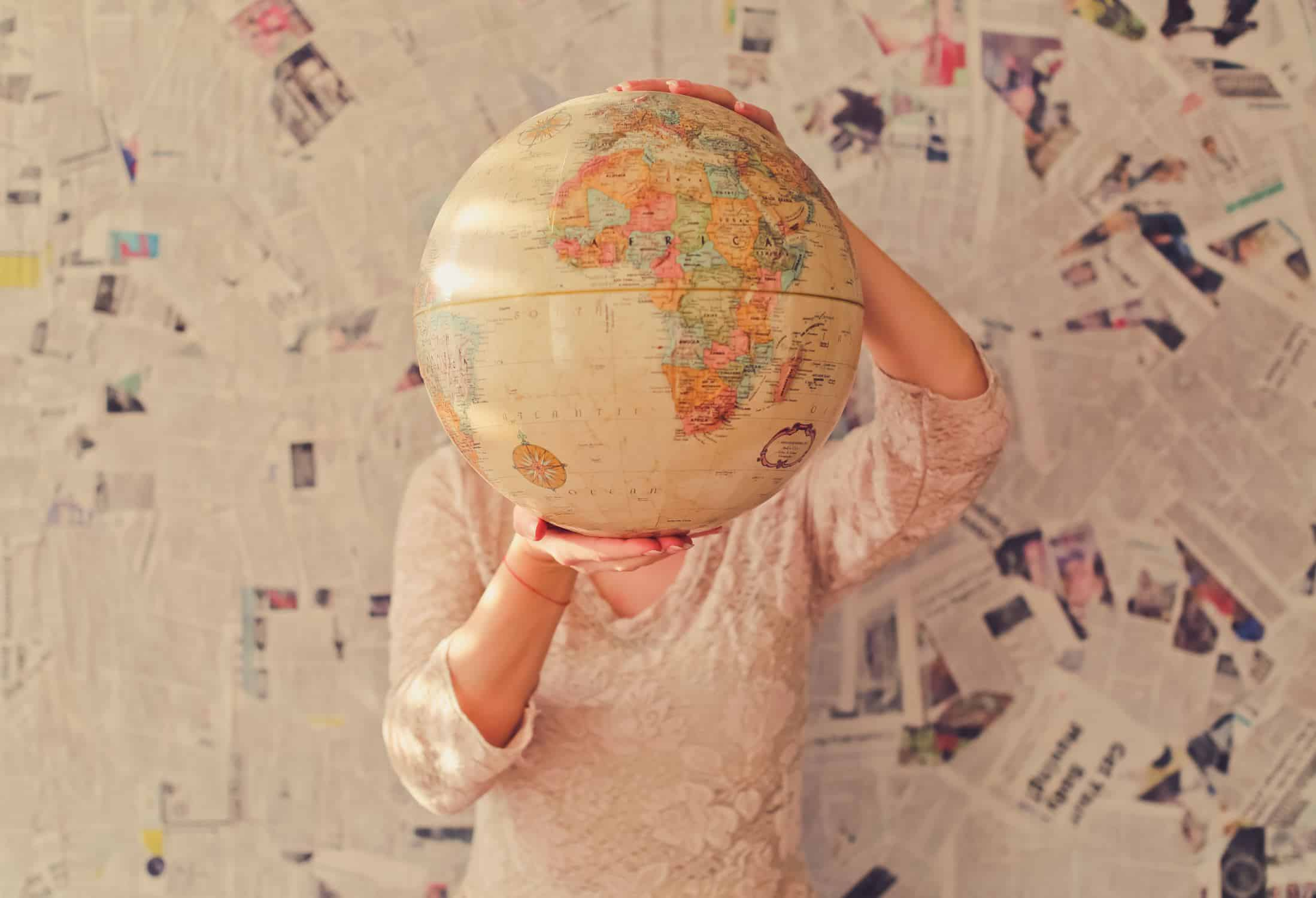 Woman holding a globe in front of her face with newspapers behind her