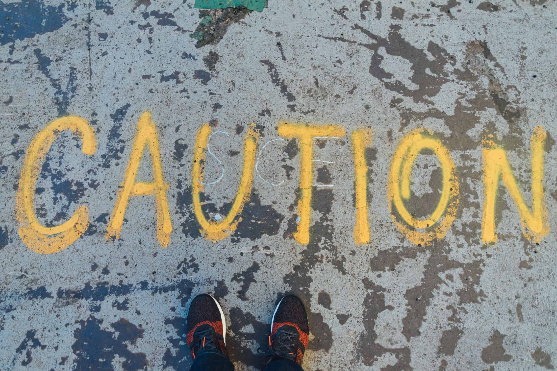 "Caution written on the ground. Perspective from above. Shoes standing beside ""caution"""